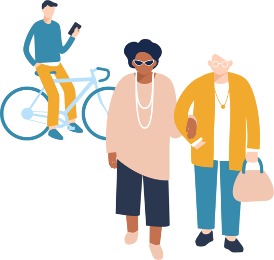 Two older women walk hand in hand while a young man on a bicycle checks his phone behind them.